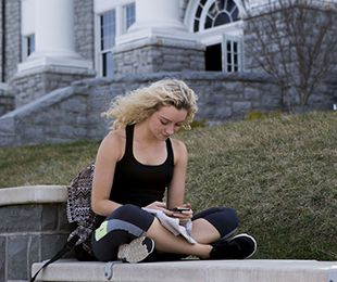 girl reading a book in front of Wilson Hall